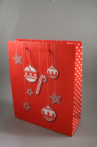 christmas gift bag with white bauble and star design red corded handles and polka dot side